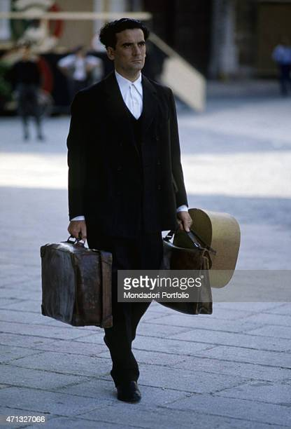 Italian actor and director Massimo Troisi holding some suitcases in the film Le vie del Signore sono finite 1987