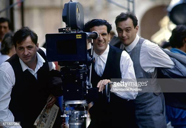 Italian actor and director Massimo Troisi using a camera on the set of the film Le vie del Signore sono finite beside Italian actor and scenarist...