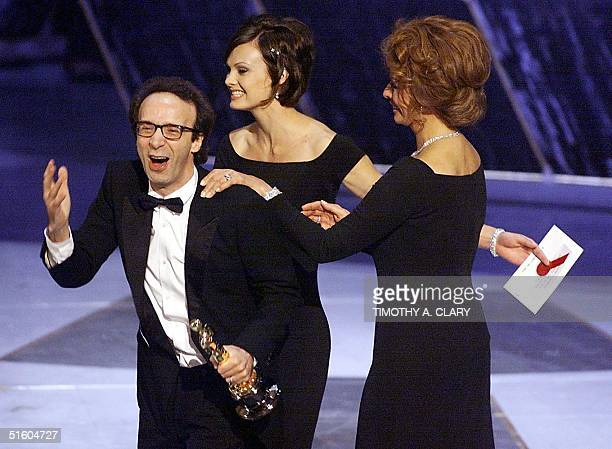 Italian actor and director Roberto Benigni is congratulated by Italian actress Sophia Loren after receiving the Oscar for Best Foreign Language Film...