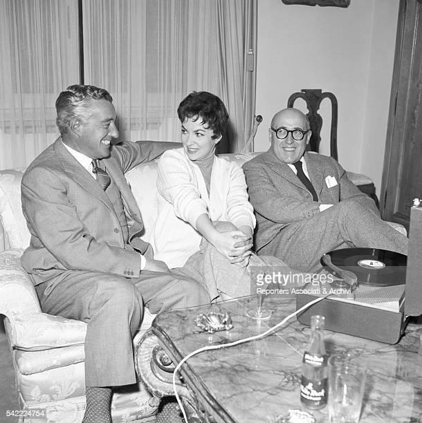 Italian actor and director Vittorio De Sica Italian actress Gina Lollobrigida and Italian screenwriter Cesare Zavattini sitting on a sofa and looking...