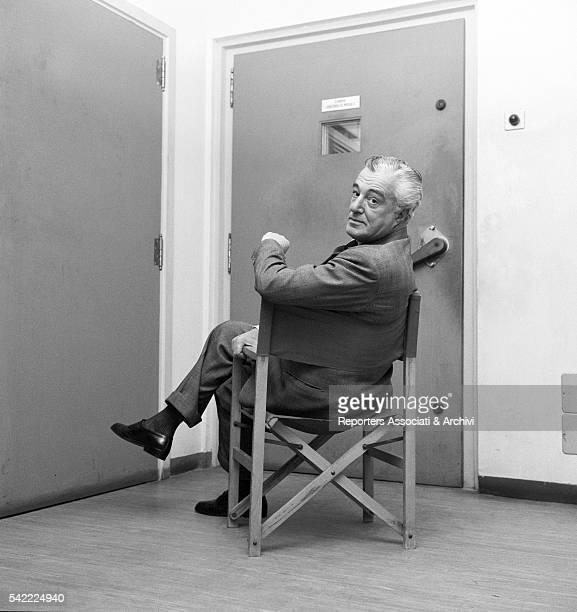 Italian actor and director Vittorio De Sica on his director's chair in front of a closed door 1962