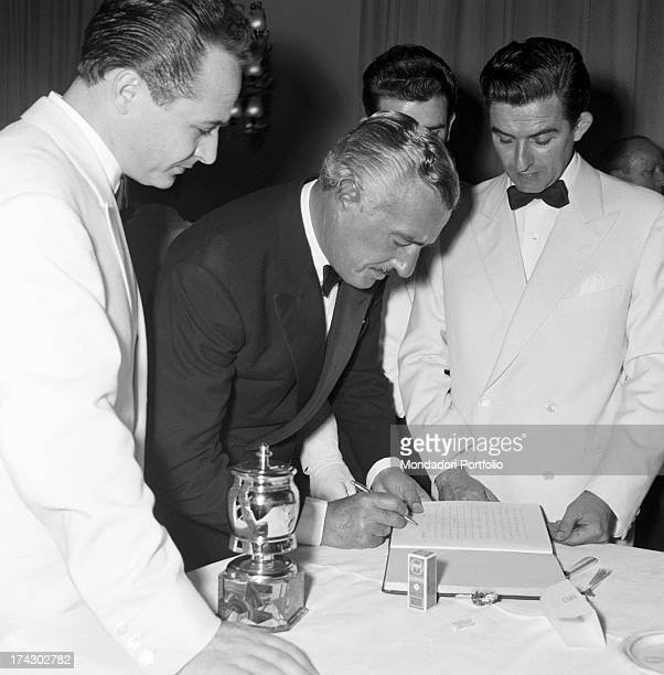 Italian actor and director Vittorio De Sica signing the guest book in a restaurant on the occasion of Grolla d'Oro Prize 1955 that he won...