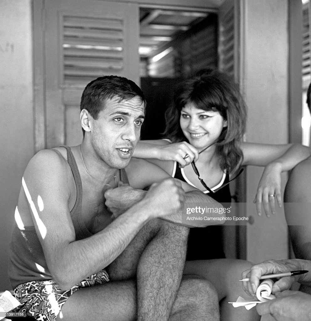 Italian actor and singer Adriano Celentano wearing an undershirt and a swimming suit sitting crosslegged next to a girl and relaesing an interview...