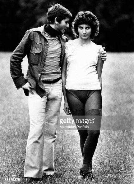 Italian actor and singer Gianni Morandi posing on the grass with Italian actress Paola Pitagora wearing leotard and leg warmers They're in the...