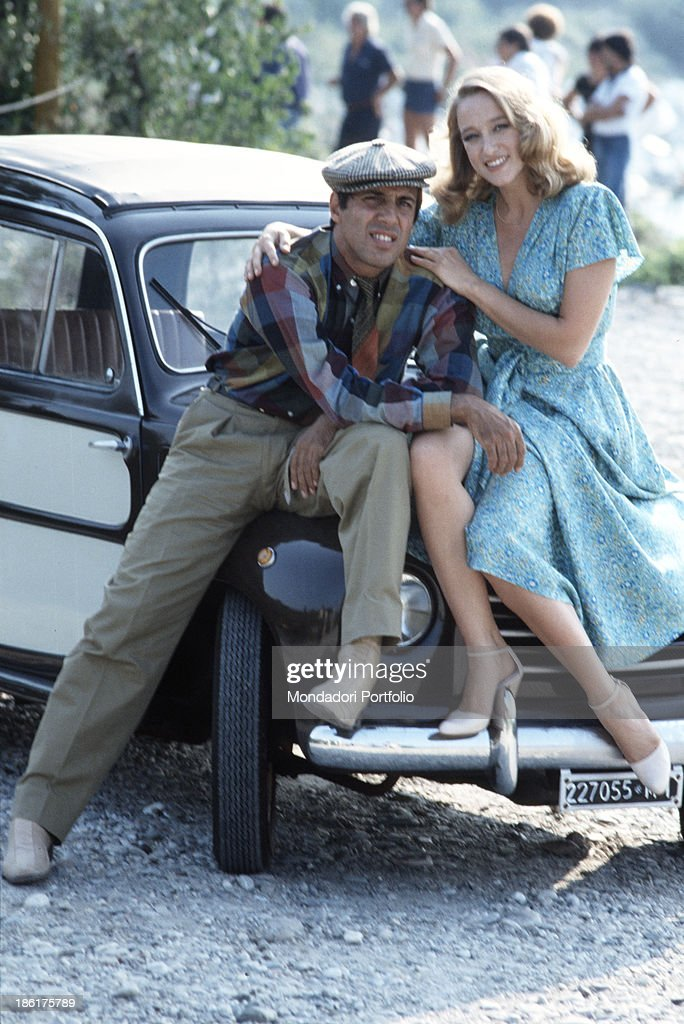 Italian actor and singersongwriter Adriano Celentano and Italian actress Eleonora Giorgi sitting on a car bonnet on the set of the film Velvet hands...