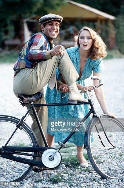 Italian actor and singersongwriter Adriano Celentano getting off a bicycle and laughing while Italian actress Eleonora Giorgi looking into the camera...