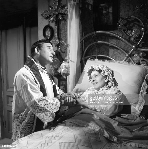 Italian actor and songwriter Renato Rascel dressed as a priest consoling Italian actress Tina Pica in bed in La nonna Sabella 1957