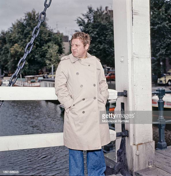 Italian actor and writer Paolo Villaggio keeping his hands in pockets on a bridge on the set of the film Strange Occasion Amsterdam 1976