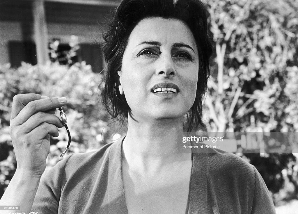 Italian actor Anna Magnani holding up a wristwatch in a still from the film 'The Rose Tattoo' directed by Daniel Mann