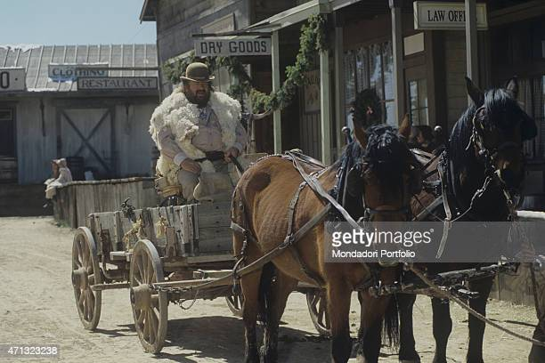 Italian actor Bud Spencer driving a cart drawn by two horses in the film Troublemakers Santa Fe 1994