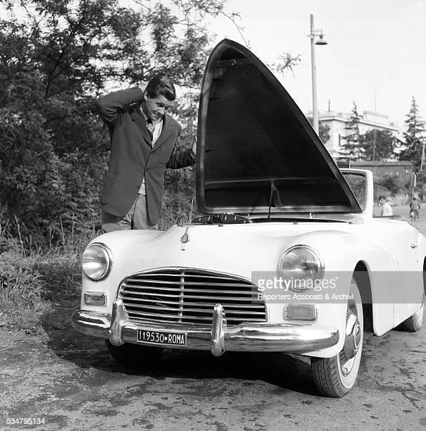 Italian actor Carlo Mazzoni posing with a Fiat Italy 1954