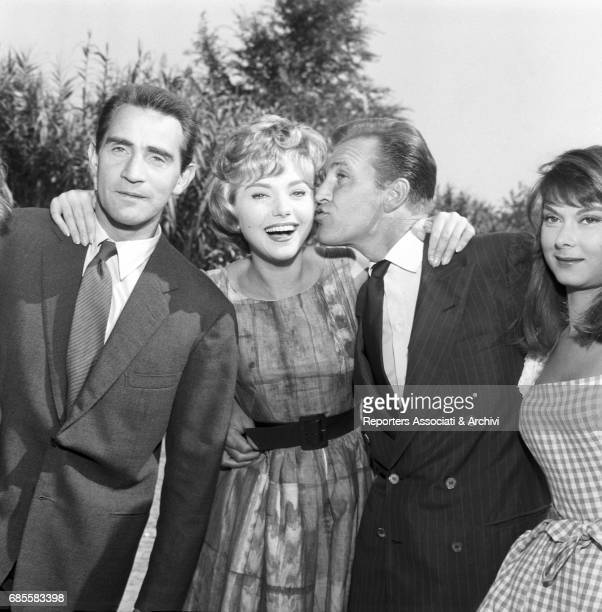 Italian actor comedian and TV host Walter Chiari posing hugging Italian actress Sylva Koscina beside the actors Franco Fabrizi and Dorian Gray during...
