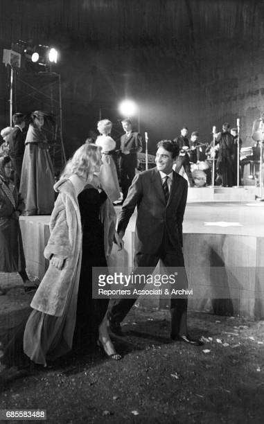 Italian actor comedian and TV host Walter Chiari walking with Swedishborn Italian actress Anita Ekberg during a break on the set of 'La dolce vita'...