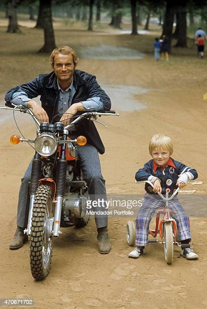 'Italian actor director scriptwriter and TV producer Terence Hill smiling on a motorcycle beside his son Jess Hill on a tricycle 1975 '