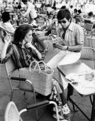 Italian actor Enzo Cerusico is seated at a table outside a coffee bar with Italian actress Tiziana Casetti she smokes a cigarette while he is reading...