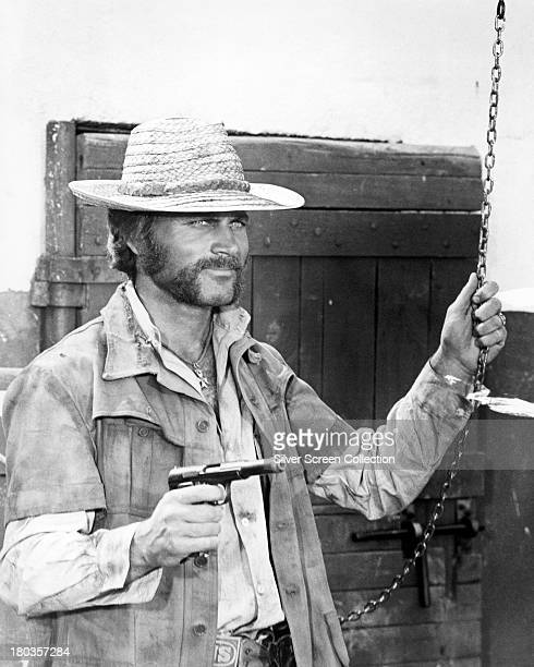 Italian actor Terence Hill wearing a straw hat and holding a pistol in an unidentified film role circa 1972