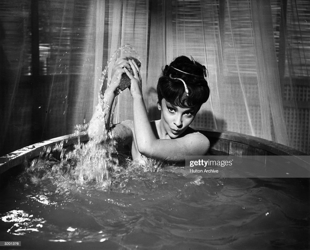 Italian actor <a gi-track='captionPersonalityLinkClicked' href=/galleries/search?phrase=Gina+Lollobrigida&family=editorial&specificpeople=93465 ng-click='$event.stopPropagation()'>Gina Lollobrigida</a>, wearing nothing but a snake hair ornament, throws water over her shoulder with a sponge while taking a bath in a wooden barrel, in a still from director King Vidor's film, 'Solomon and Sheba.'