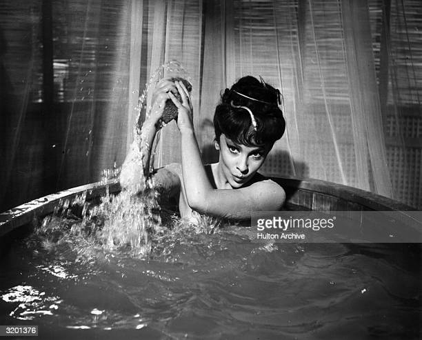 Italian actor Gina Lollobrigida wearing nothing but a snake hair ornament throws water over her shoulder with a sponge while taking a bath in a...