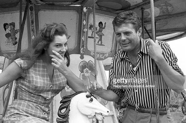 Italian actor Marcello Mastroianni and Italian actress Rosanna Schiaffino smiling on a merrygoround in the film Piece of the Sky 1957