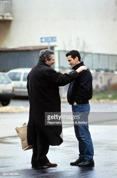 Italian actor Marcello Mastroianni putting his hand on Italian actor Massimo Troisi's shoulder during a break on the set of the film What Time Is It...