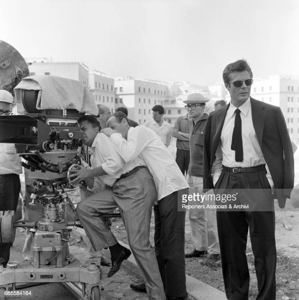 Italian actor Marcello Mastroianni waiting while Italian director Federico Fellini looks through a camera during a break on the set of La dolce vita...