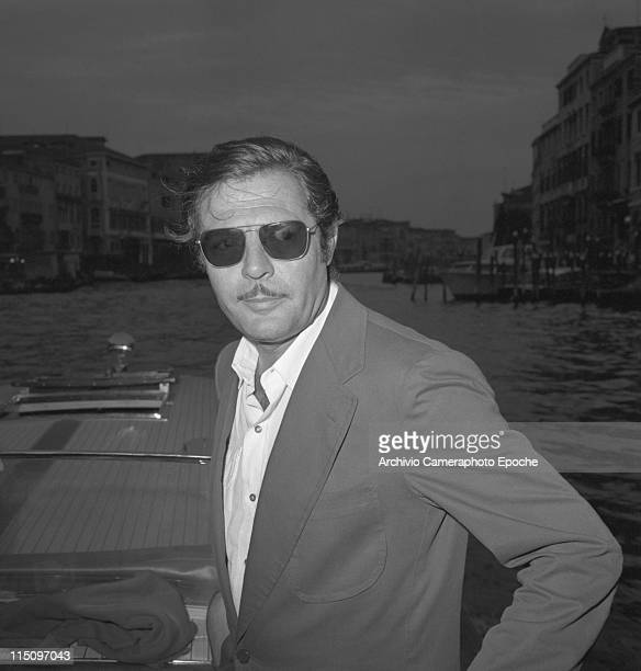 Italian actor Marcello Mastroianni wearing a blazer and sunglasses portrayed on a water taxi on a trip along the Grand Canal in Venice for the Cinema...