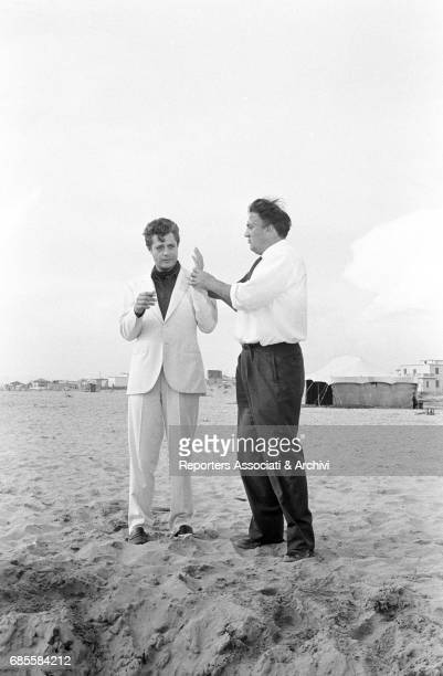 Italian actor Marcello Mastroianni with Italian director Federico Fellini on the beach of Passoscuro hamlet of Fiumicino on the set of La dolce vita...