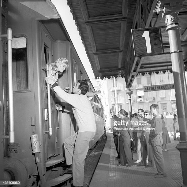 Italian actor Maurizio Arena greeting a girl at the railway station of Napoli Mergellina in a scene from the film Avventura a Capri Napoli 1958