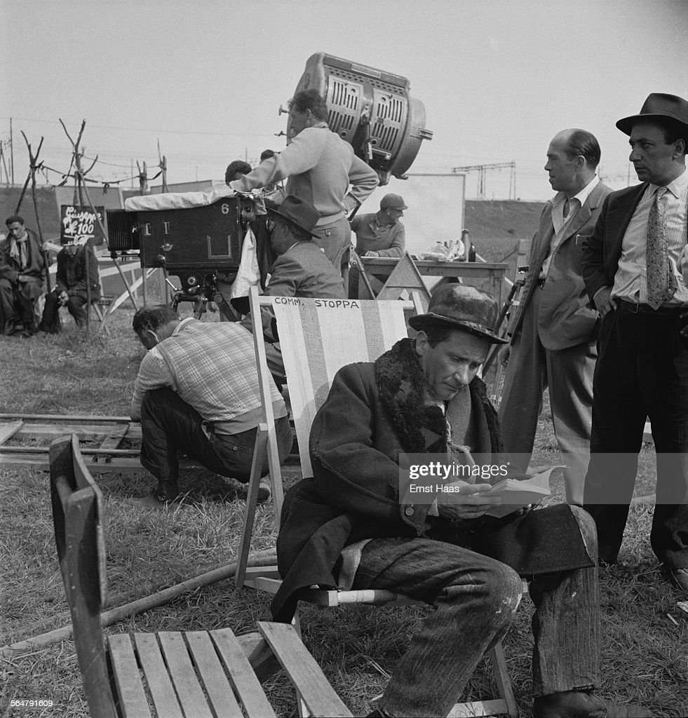 Italian actor Paolo Stoppa (1906 - 1988) reading on the set of the film 'Miracolo a Milano' ('Miracle in Milan') in Italy, 1951. Director Vittorio De Sica is visible behind him.