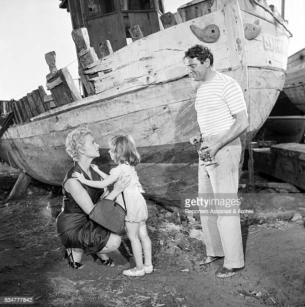 Italian actor Raf Vallone posing with French actress Martine Carol and little Anna Pisani on the set of The Beach Italy 1953