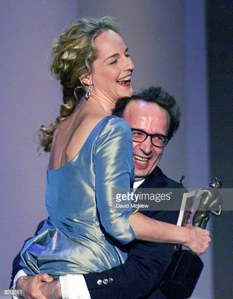 Italian actor Roberto Benigni joyously lifts actress Helen Hunt who hold his award for Outstanding Perfomance by a Male Actor in a Leading Role at...