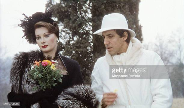 Italian actor singer and songwriter Adriano Celentano giving some flowers to Frenchborn Italian actress Edwige Fenech in the film Ace Italy 1981