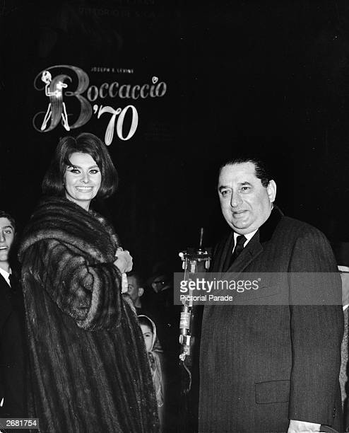 Italian actor Sophia Loren and producer Joseph E Levine president of Embassy Pictures activate a neon sign to promote the film 'Boccaccio '70' at...