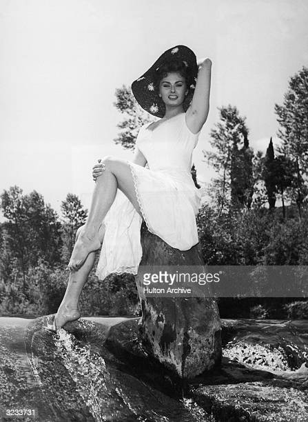 Italian actor Sophia Loren poses barefoot on a rock in a stream in a promotional portrait for the film 'The Miller's Beautiful Wife' directed by...