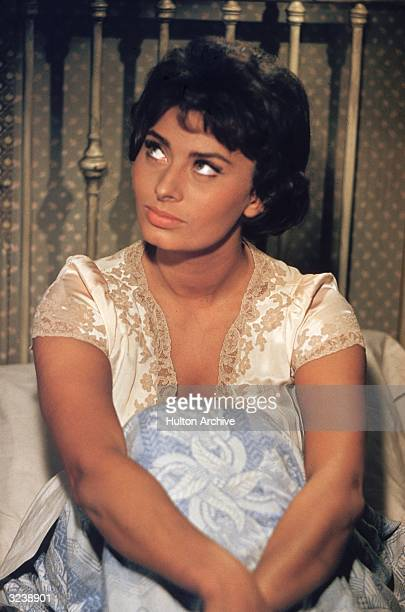 Italian actor Sophia Loren wearing a nightgown sits in bed in a still from the film 'Houseboat'