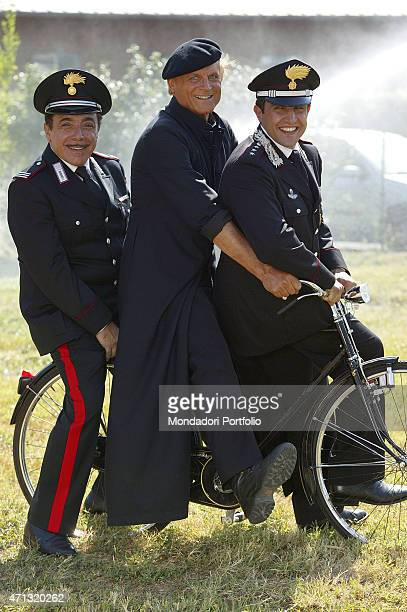 Italian actor Terence Hill as the parish priest of the village in Umbria sitting on the saddle of his bicycle with Italian actors Nino Frassica and...