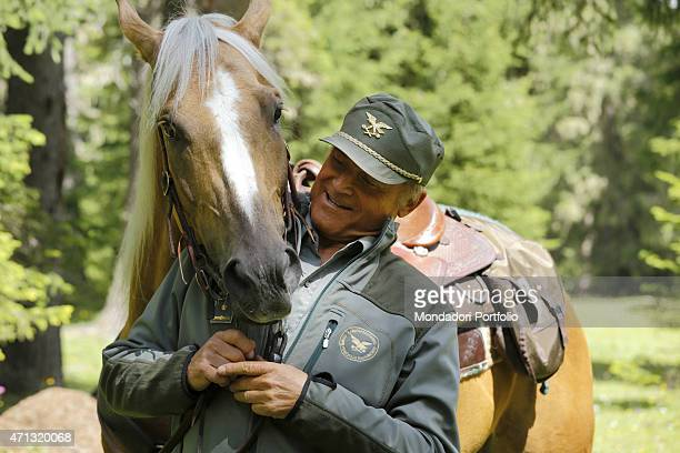 Italian actor Terence Hill as the State Forestry Corps Chief inspector Pietro standing beside a horse and looking at its snout in a photo shooting on...
