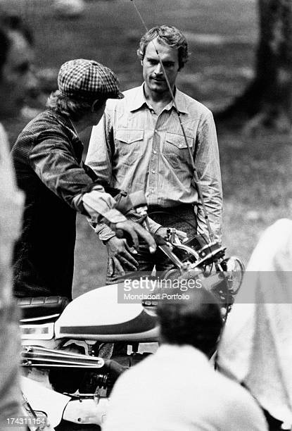 Italian actor Terence Hill talking to a man leaning on a motorcycle on the set of the film Watch Out We're Mad Rome 1974