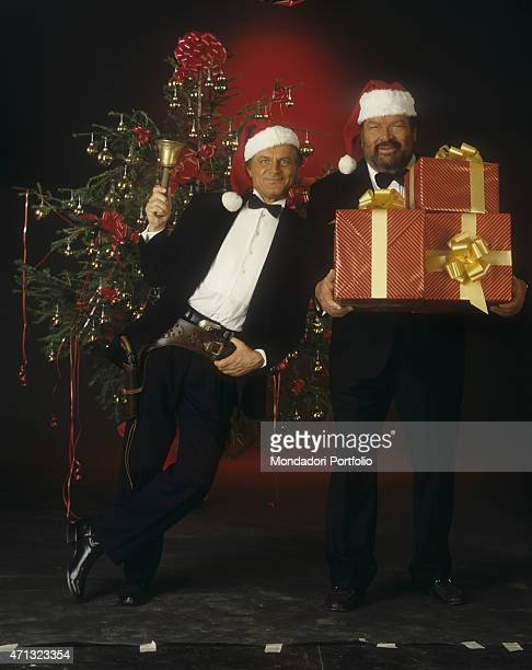 Italian actor Terence Hill with a Santa Claus hat posing shoulder to shoulder with Italian actor Bud Spencer holding some gifts They're the main...