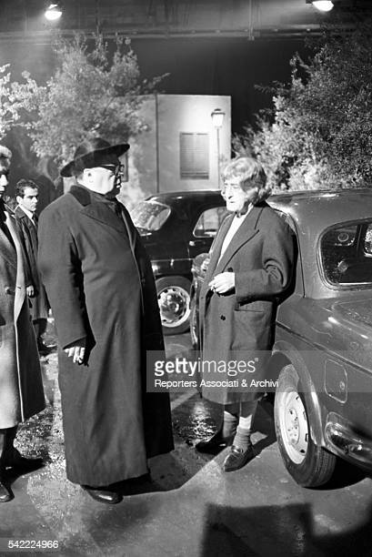 Italian actor Tot˜ disguised as a woman and Italian actor Aldo Fabrizi disguised as a priest smoking during a break on the set of Tot˜ contro i...