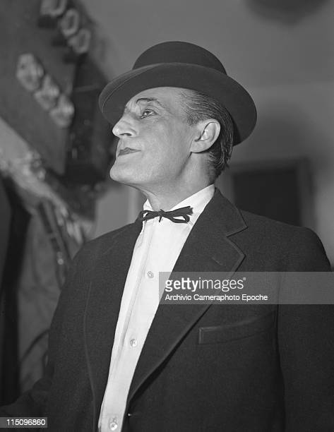Italian actor Toto Antonio De Curtis portrayed from below wearing his usual scene costume a bowler hat a blazer a white shirt and a string bow tie...