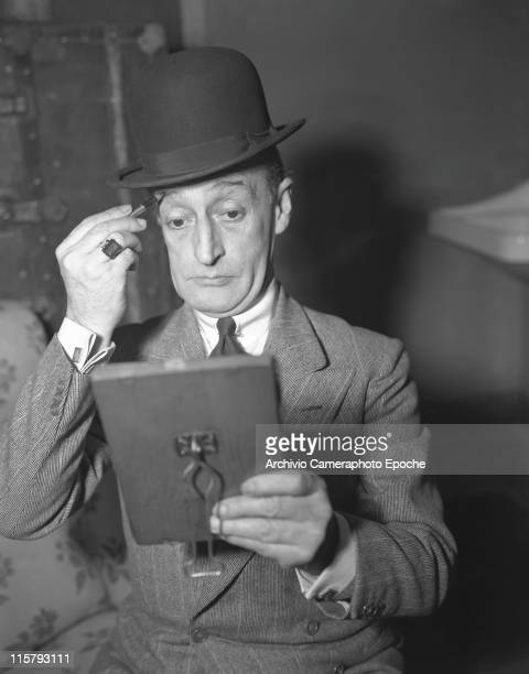 Italian actor Toto' Antonio De Curtis wearing a blazer a tie a ring and a bowler hat portayed while painting his eyebrows with a pencil and looking...