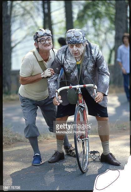 Italian actor writer and comedian Paolo Villaggio is in the saddle of a bicycle and is encouraged by Italian actor Gigi Reder in the film Fantozzi...