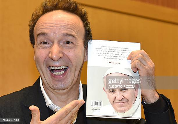 Italian actor/director Roberto Benigni smiles as he shows a copy of the pope Francis' interview book 'The name of God is Mercy' during the...