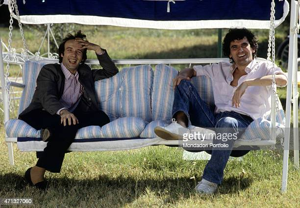 Italian actors and directors Massimo Troisi and Roberto Benigni smiling seated on a swing 1984