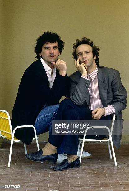 Italian actors and directors Massimo Troisi and Roberto Benigni posing seated on two children chairs 1984