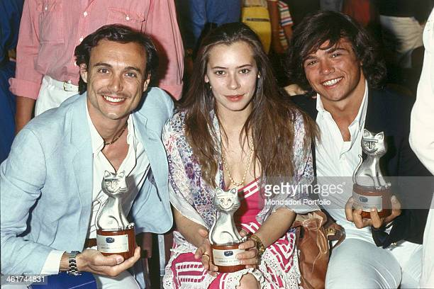 Italian actors Claudio Amendola Massimo Bonetti and Barbara De Rossi posing smiling wuth the Telegatto awards they won GiardiniNaxos 1983
