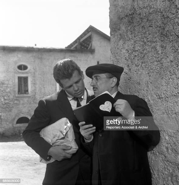 Italian actors Peppino De Filippo and Renato Salvatori fiddling through a notebook in La nonna Sabella 1957