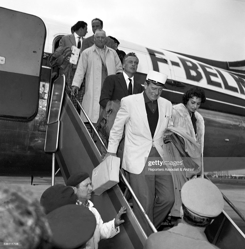 Italian actors Rossano Brazzi and Sophia Loren and American actor John Wayne walking down the aircraft ladder when arriving at Ciampino airport from...