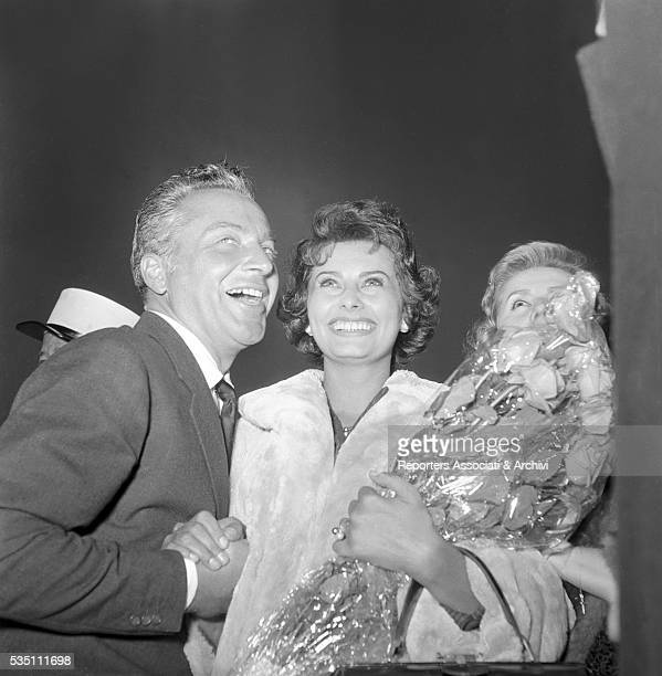 Italian actors Rossano Brazzi and Sophia Loren smiling when arriving at Ciampino airport from Libya where they shot the film Legend of the Lost Rome...